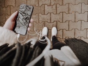 We see a smart phone in the hands of a woman standing on a sidewalk. Earbuds are plugged in. Use Veraki's visualization recordings for a boost of energy.