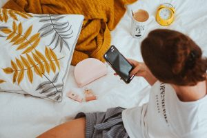 The woman sitting on her bed scrolling the social feed on her phone. Knowing your intention before getting on your phone is helpful when it comes to social media vs mindfulness.